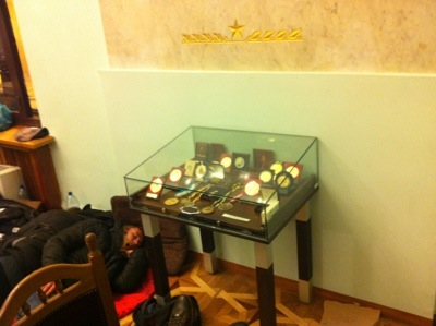 On the first floor, above the entrance, an activist sleeps under a cabinet full of sport medals