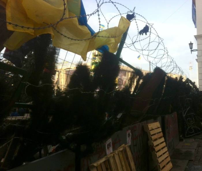 Razor wire tops the artificial Christmas tree foliage on a barricade at Independence Square