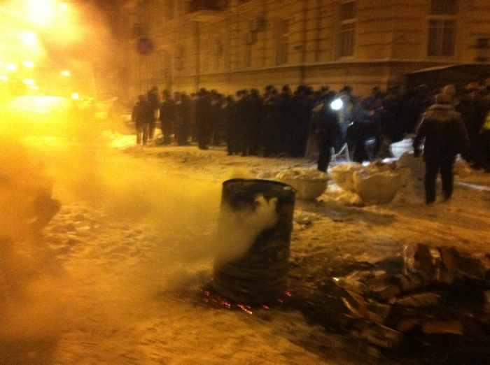 The oil drum fire used by protesters sizzles after police move to clear a small barricade