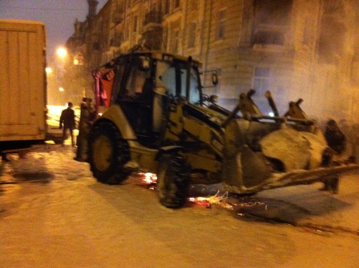 A bulldozer moves in to clear what was a fairly flimsy barricade