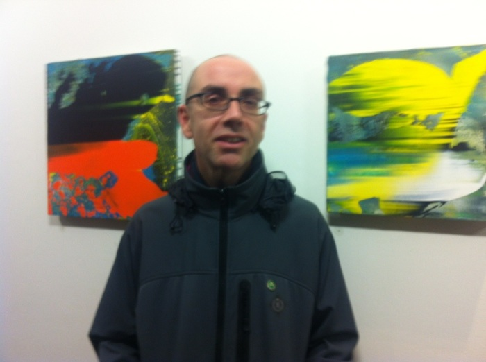 Elfyn Lewis in the middle of two of his works