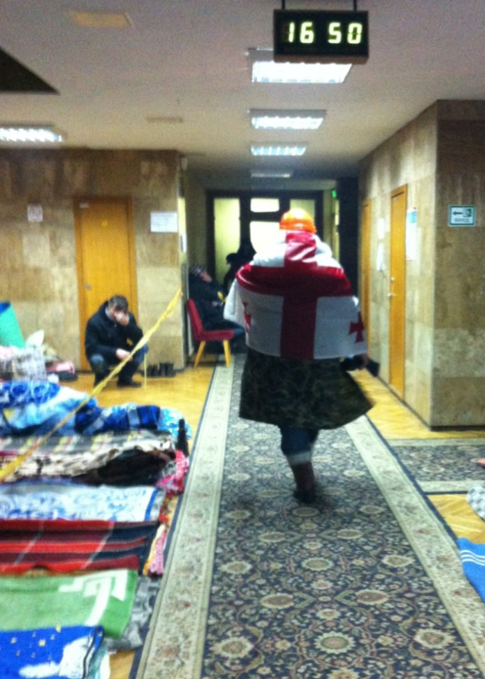 A protester wraps himself in a Georgian flag in the Trade Union offices in Independence Square